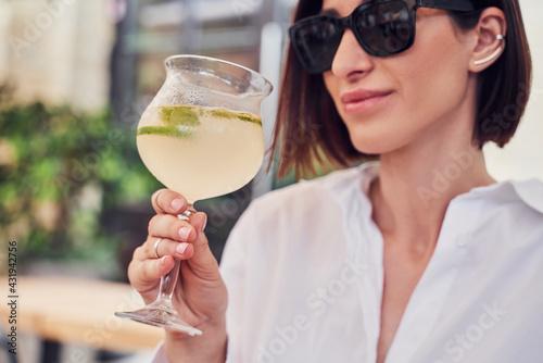 Obraz Pritty girl in glasses drinking cocktail - fototapety do salonu