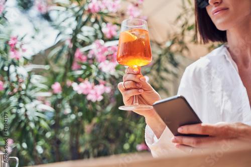 Obraz Cropped shot of attractive girl drinking aperol - fototapety do salonu
