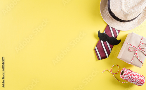 Fototapeta Happy Father's Day background concept with tie and  mustache, hat, gift box on pastel yellow background. obraz