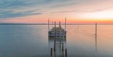 Vue D'un Ponton De Pêche Avec Un Coucher De Soleil Sur Un étang De La Camargue, Réserve Naturelle Protégée