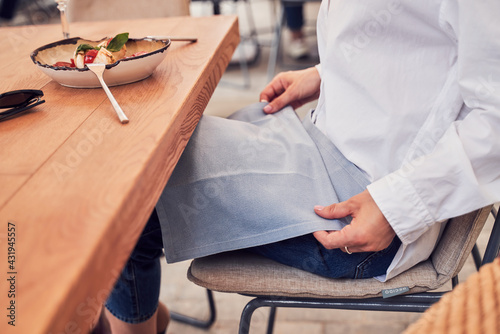 Obraz Close up of girl puting napkin on knees - fototapety do salonu