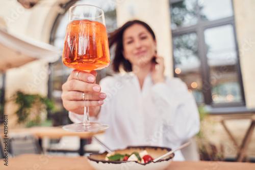 Obraz Attractive girl drinking aperol in restaurant terrace - fototapety do salonu