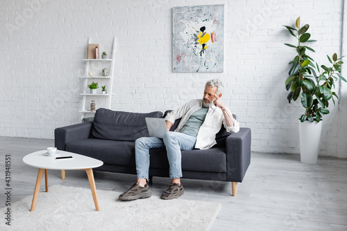 Obraz man with grey hair using laptop while sitting on couch near cup of coffee and smartphone with blank screen on coffee table. - fototapety do salonu