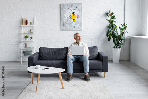 Obraz bearded man with laptop sitting on couch near cup of coffee and smartphone with blank screen on coffee table. - fototapety do salonu