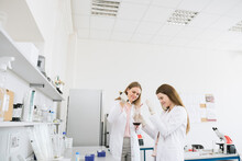 Scientists In White Coats Doing Experiment In Lab