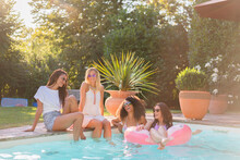 Cheerful Female Friends Having Fun In Swimming Pool During Sunny Day