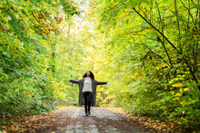 Carefree Woman With Arms Outstretched Running On Footpath In Forest