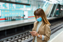 Woman With Protective Face Mask Using Mobile Phone While Standing At Subway Station During Pandemic