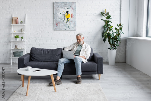 Obraz smiling man with laptop sitting on couch near cup of coffee and smartphone with blank screen on coffee table. - fototapety do salonu