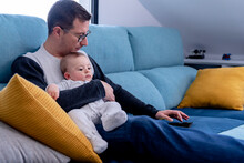 Father Using Tablet While Sitting With Baby Boy On Sofa In Living Room
