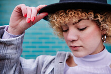 Curly Haired Woman With Eyes Closed Holding Hat