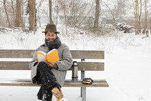 Smiling Man Reading Book While Sitting On Bench During Winter