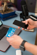 Businessman With Credit Card Doing Shopping Over Mobile Phone At Home