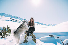 Young Woman With Her Dog In Snow Covered Land Against Clear Sky