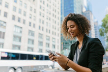 Smiling Afro Businesswoman Using Smart Phone In City