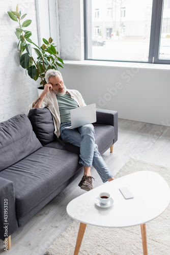 Obraz man with grey hair sitting on couch and using laptop in living room. - fototapety do salonu