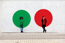 Two Circles Visualizing Social Distancing Covering Man And Woman Standing Outdoors With Smart Phones In Hands