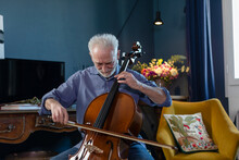 Senior Man Playing Cello While Sitting In Living Room At Home