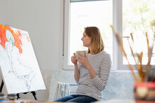 Woman With Coffee Cup Looking At Painting While Sitting In Home Studio