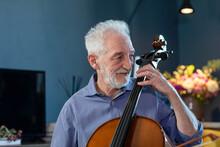 Smiling Senior Man Playing Cello At Home