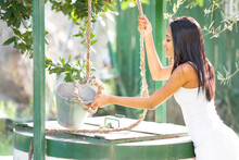 Woman Pulling Rope Tied To Bucket At Water Well While Gardening In Backyard