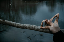 Young Woman With Eyes Closed Leaning On Fallen Tree Against Lake