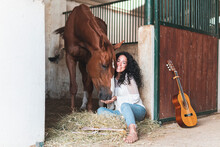 Smiling Woman With Guitar Feeding Horse While Sitting In Stable