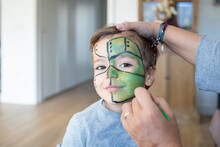 Boy With Mask Painted On Face At Home During Christmas