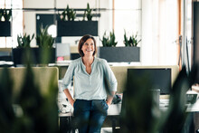Smiling Businesswoman With Hands In Pockets Leaning On Desk At Office