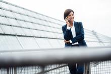 Female Entrepreneur Talking On Smart Phone Outside Office Building