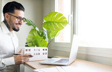 Smiling Male Architect Holding Model During Video Call Through Laptop At Desk In Office