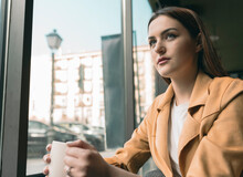 Beautiful Woman Sitting By Glass Window At Coffee Shop