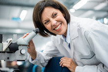 Smiling Female Scientist Holding Microscope At Laboratory