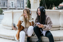 Laughing Female Friends Taking Selfie Wearing Headphones While Sitting Against Fountain