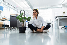 Female Engineer With Hand On Chin Sitting On Floor In Industry