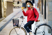 Young Woman Wearing Face Mask Mask Using Mobile Phone While Sitting With Bicycle On Footpath