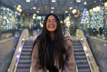 Cheerful Young Woman Standing Against Illuminated Glass Wall In Shopping Mall
