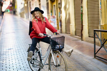 Excited Woman Riding Bicycle On Footpath In City