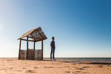 Man Looking At Sea View While Standing On Beach During Sunny Day