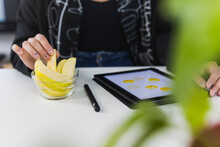 Young Female Design Professional With Digital Tablet Having Apple While Working At Studio