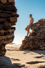 Shirtless Man Looking Away While Leaning On Stone Wall At Beach
