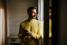 Contemplating Man Looking Through Window While Holding Mobile Phone At Home