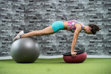 Young Sportswoman Exercising With Fitness Ball At Health Club