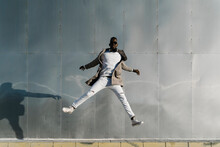 Man Jumping By Metallic Wall