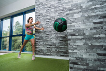 Sportswoman Exercising With Medicine Ball In Gym