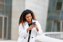 Smiling Woman Using Smart Phone While Leaning By Retaining Wall