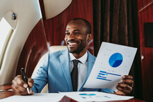 Smiling Businessman Looking Away While Holding Pie Chart In Airplane