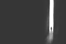 Illustration Of Man Getting Out Of Darkness Through A Light Door, Surreal Concept Black And White