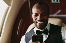 Smiling Businessman Text Messaging On Smart Phone In Private Jet