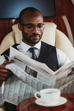 Male Entrepreneur Reading Newspaper In Airplane